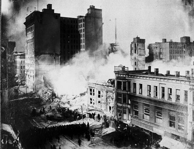 Fire fighters on Main Street using hoses in an attempt to douse the embers of the February 26, 1904 Sibley Fire. In this view, the Granite building is to the left. This photo was actually taken the day after the fire from the top of the Whitcomb House (Feb. 27, 1904).
